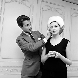 Fashion designer Halston fitting a model with a white fur hat